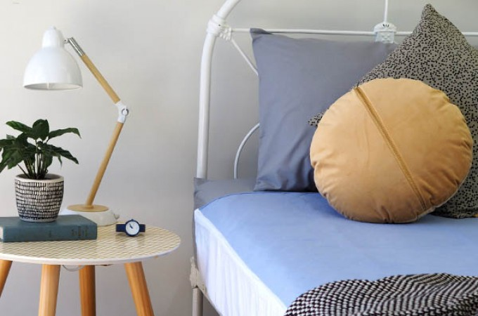Close up image of bed and side table with Conni Bed Pad exposed