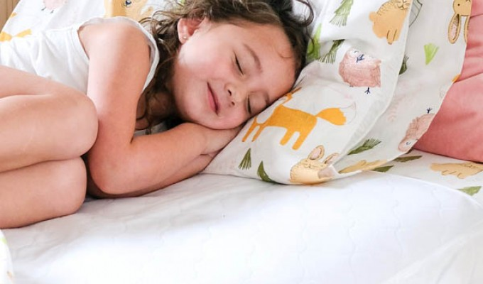 Child sleeping on Conni Bed Pad in white