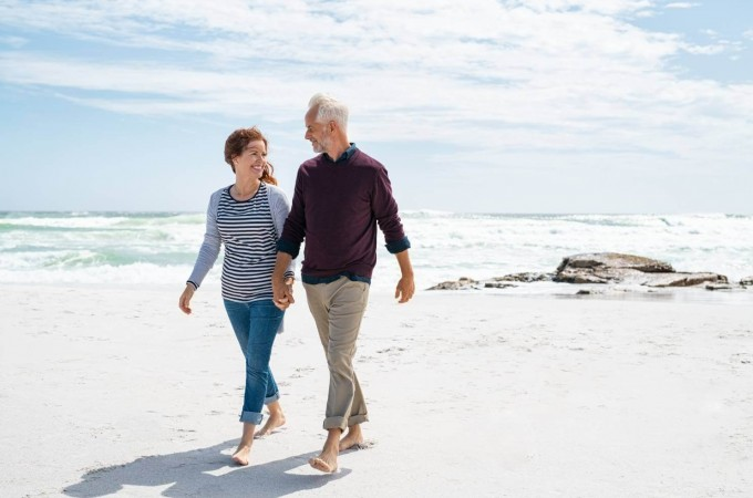 Two adults walking on beach holding hands