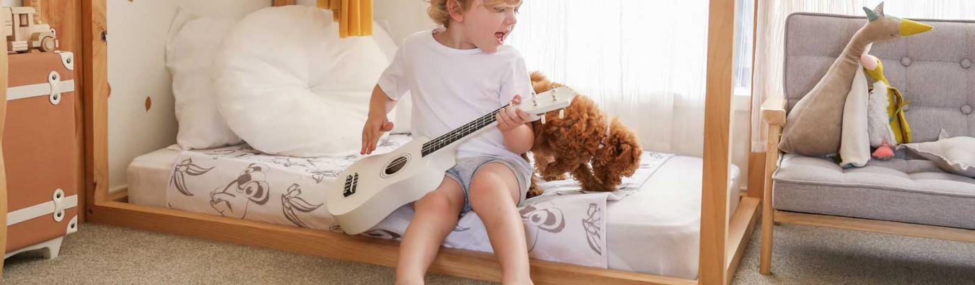 Child on Conni Kids Bed Pad playing guitar